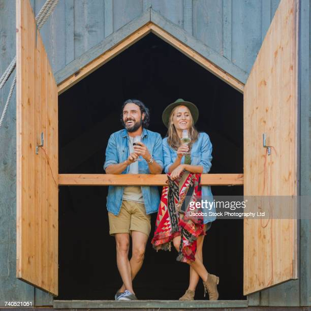 Hispanic couple standing near open barn doors drinking wine