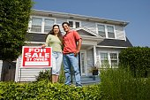 Hispanic couple standing next to For Sale sign in front of house