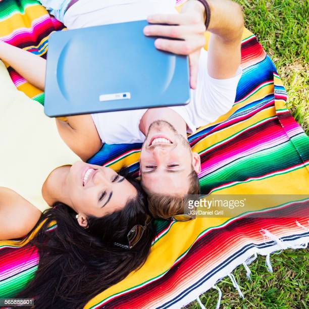 Hispanic couple taking selfie on blanket in park