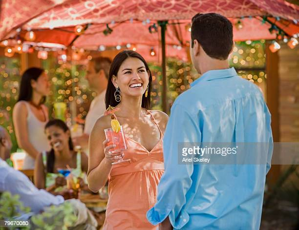 Hispanic couple talking at party