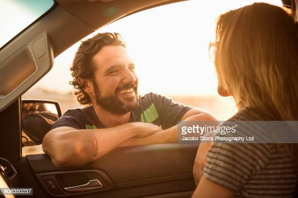 Hispanic couple talking in car