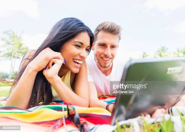 Hispanic couple using digital tablet on blanket in park