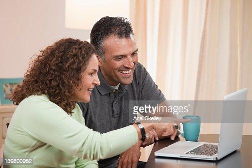 Hispanic couple using laptop together : Stock Photo