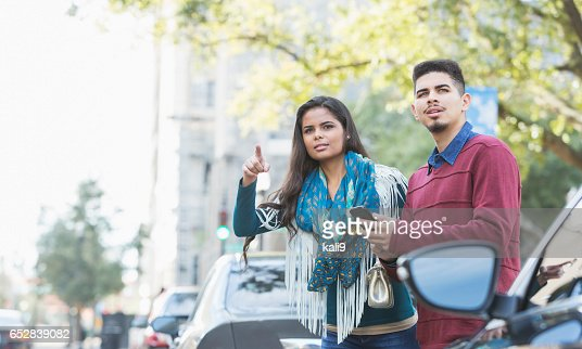 Hispanic couple waiting for a car to pick them up : Photo
