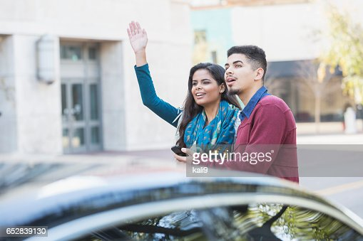 Hispanic couple waiting for a car to pick them up : Stockfoto