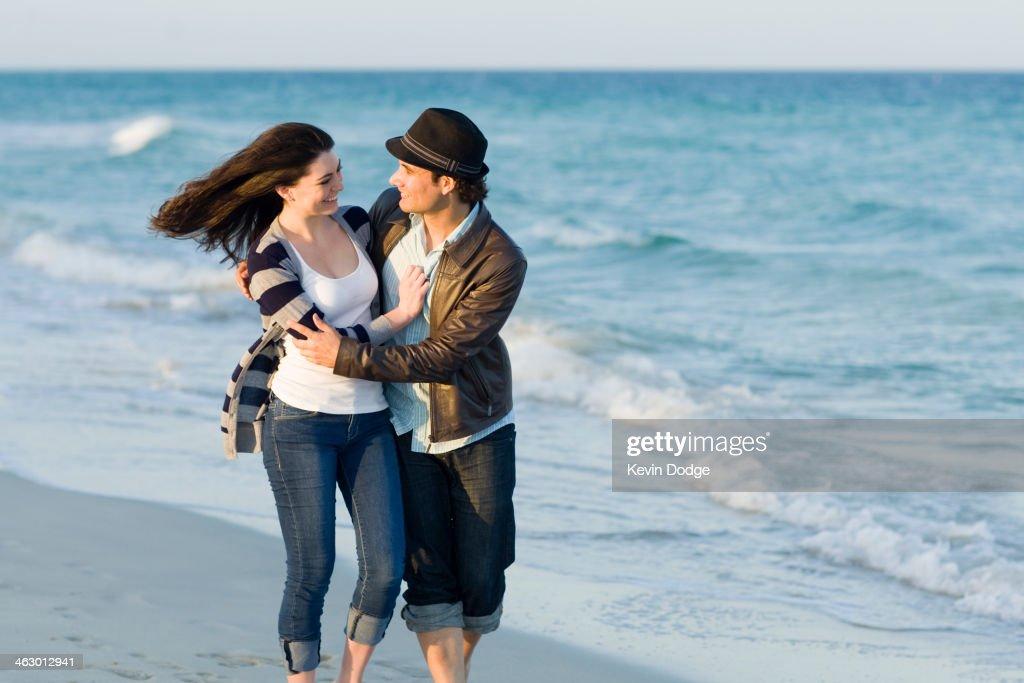 Hispanic couple walking on beach : Stock Photo