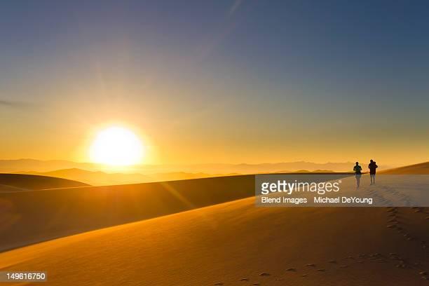 Hispanic couple walking on sand dune at sunset
