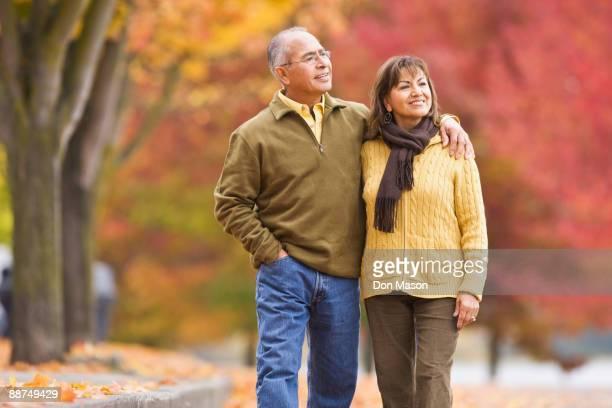 Hispanic couple walking outdoors in autumn