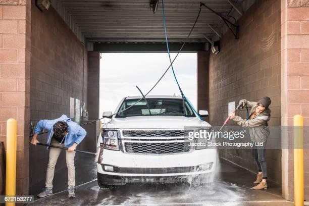 Hispanic couple washing car at self-serve car wash