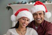 Hispanic couple wearing Santa Claus hats
