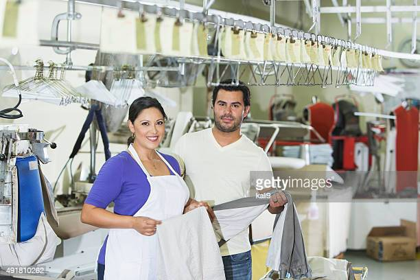 Hispanic couple working in dry cleaner