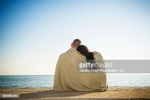Hispanic couple wrapped in blanket on beach