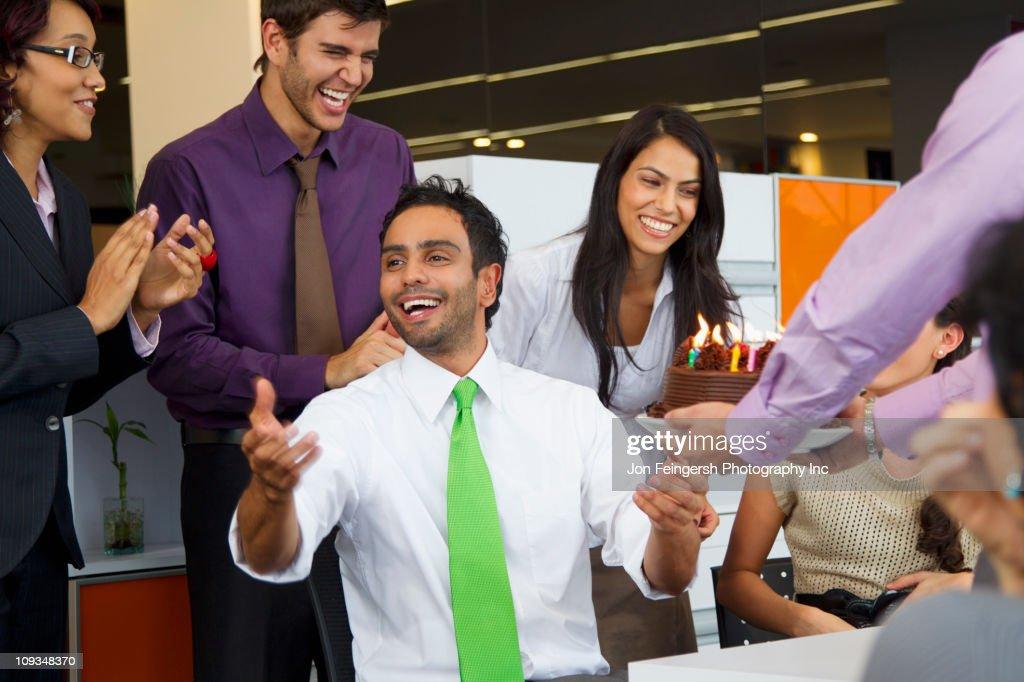 Hispanic co-workers surprising businessman with birthday cake