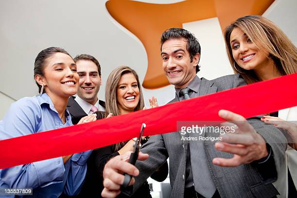 Hispanic co-workers watching businessman cutting red ribbon