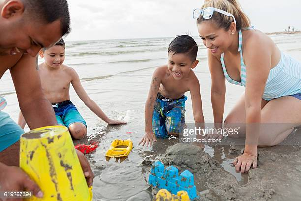 Hispanic dad helps his sons build sandcastle