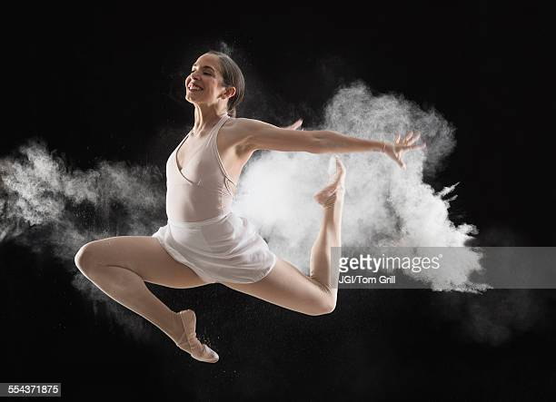 Hispanic dancer leaping in cloud