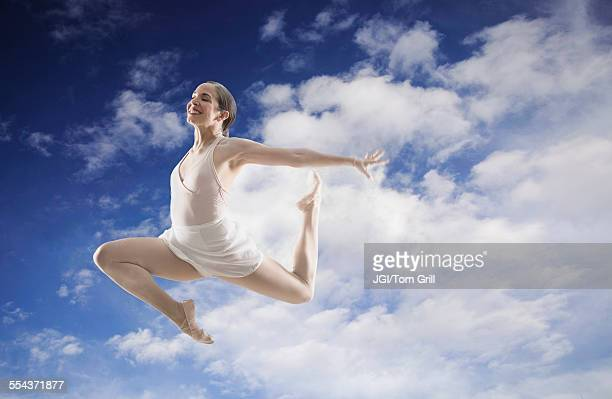 Hispanic dancer leaping in cloudy blue sky