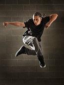 Hispanic dancer leaping in mid air