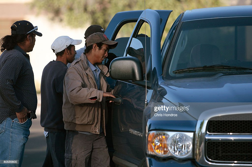 Hispanic day laborers open the doors to a truck as a man hires them to work manual labor April 5, 2008 in Tucson, Arizona. Manual laborers, mostly undocumented workers from Mexico, frequent this corner in Tucson every morning before dawn, in an informal arrangement with local employers, who can pick up as many as they need for day-long jobs. Much of the work up to now has been housing-related; but with the housing downturn, that work has largely dried up, and these laborers now often don't work more than once a week.