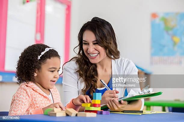 Hispanic daycare teacher works with little girl playing blocks
