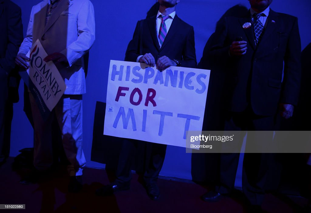 A hispanic delegate holds a sign at the Republican National Convention (RNC) in Tampa, Florida, U.S., on Thursday, Aug. 30, 2012. Republican presidential nominee Mitt Romney, a wealthy former business executive who served as Massachusetts governor and as a bishop in the Mormon church, is under pressure to show undecided voters more personality and emotion in his convention speech tonight, even as fiscal conservatives in his own party say he must more clearly define his plans for reining in the deficit and improving the economy. Photographer: Daniel Acker/Bloomberg via Getty Images