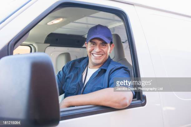 Hispanic deliveryman driving van