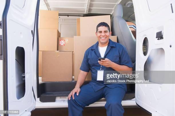 Hispanic deliveryman sitting in back of van