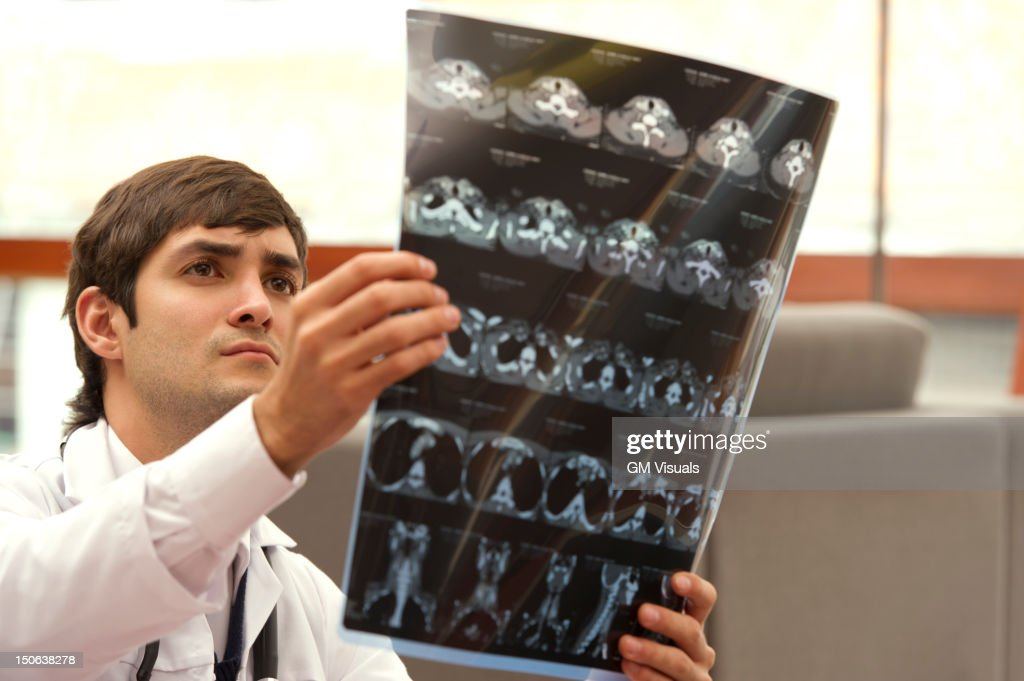 Hispanic doctor examining CAT scan