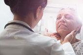 Hispanic doctor examining older patient