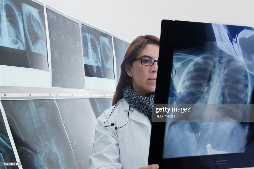 Hispanic doctor examining x-rays in hospital