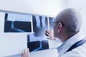 Hispanic doctor examining x-rays