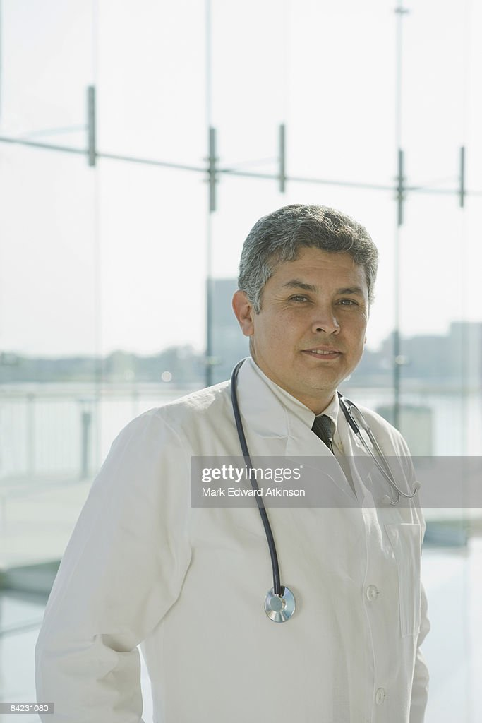 Hispanic doctor in lab coat and stethoscope : Stock Photo