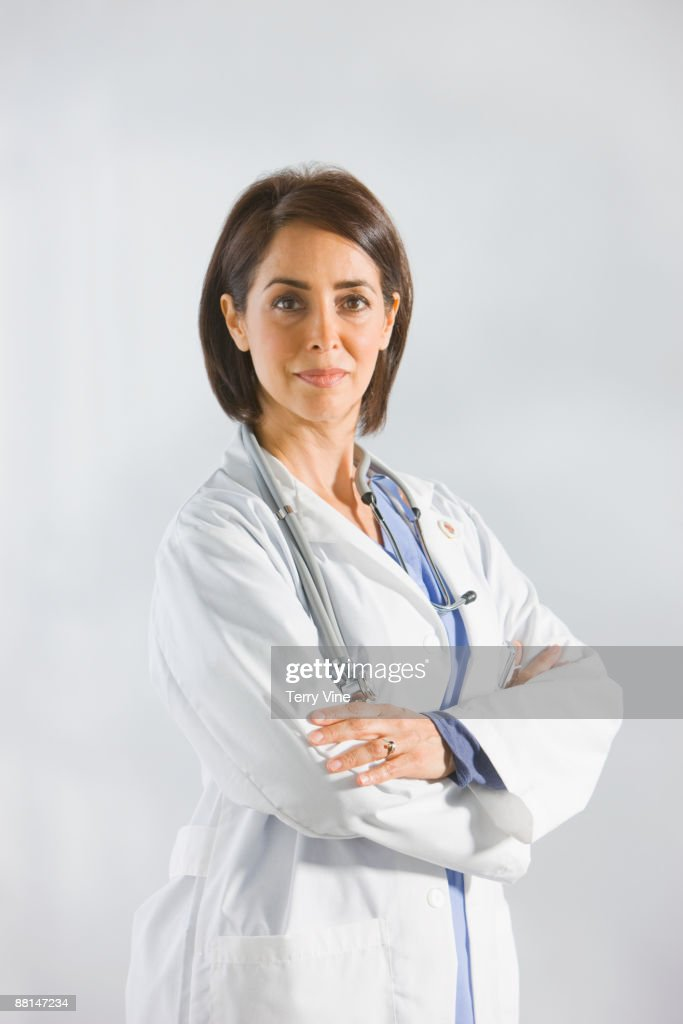 Hispanic doctor in lab coat with arms crossed : Stock Photo