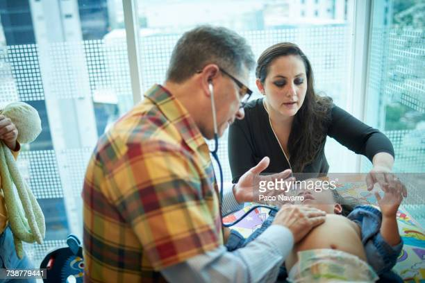 Hispanic doctor listening to chest of girl with Down Syndrome