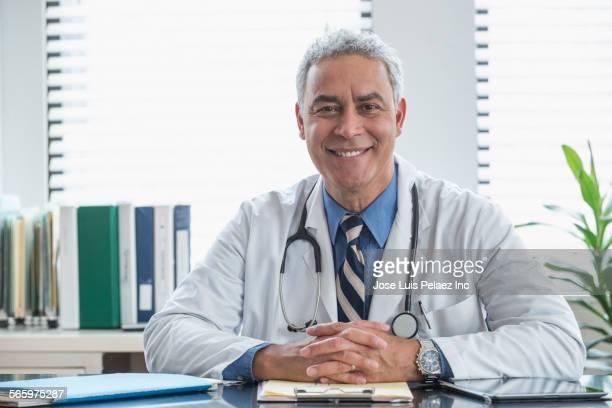 Hispanic doctor smiling at office desk