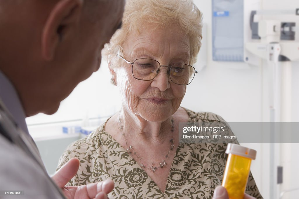 Hispanic doctor talking with older patient : Stock Photo