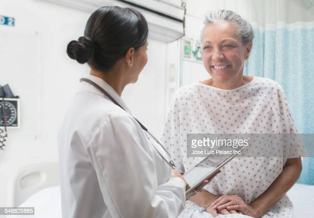 Hispanic doctor using digital tablet and talking to older patient