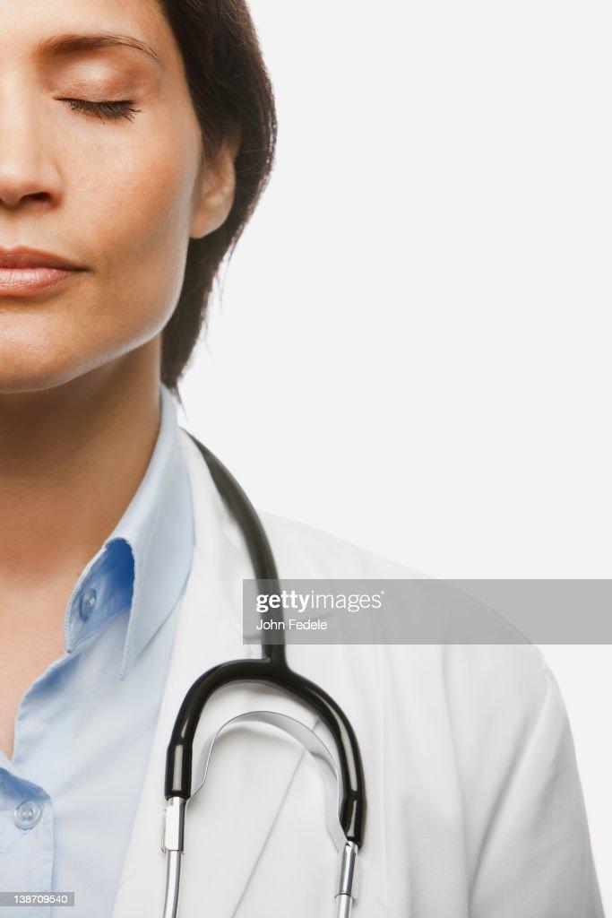 Hispanic doctor with eyes closed : Stock Photo