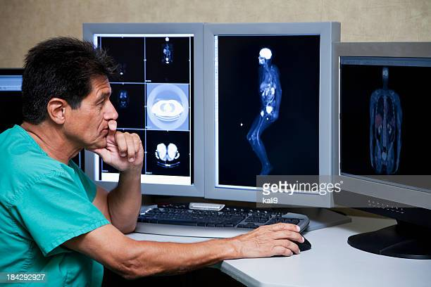 Hispanic doctor with medical scans