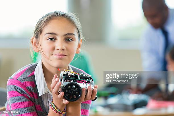 Hispanic elementary girl building robot during after school science club