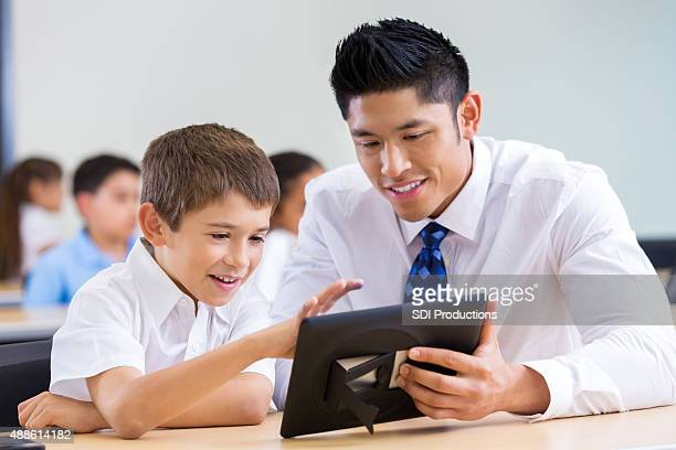 Hispanic elementary student learning about digital tablet with teacher