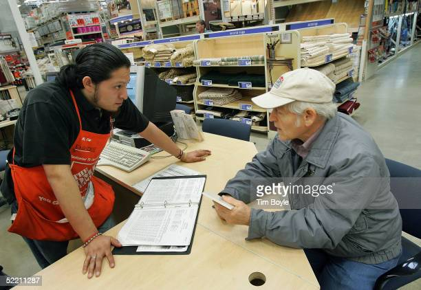 Hispanic employee Enrique Tototzintle assists customer Bob Baime at The Home Depot store February 17 2005 in Evanston Illinois The world's largest...