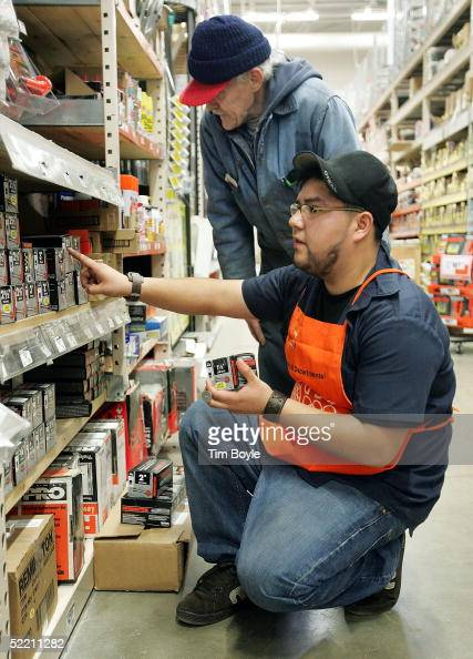 Hispanic employee Gerardo Hernandez assists customer Ed Topp at The Home Depot store February 17 2005 in Evanston Illinois The world's largest home...