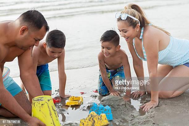 Hispanic family builds sandcastle