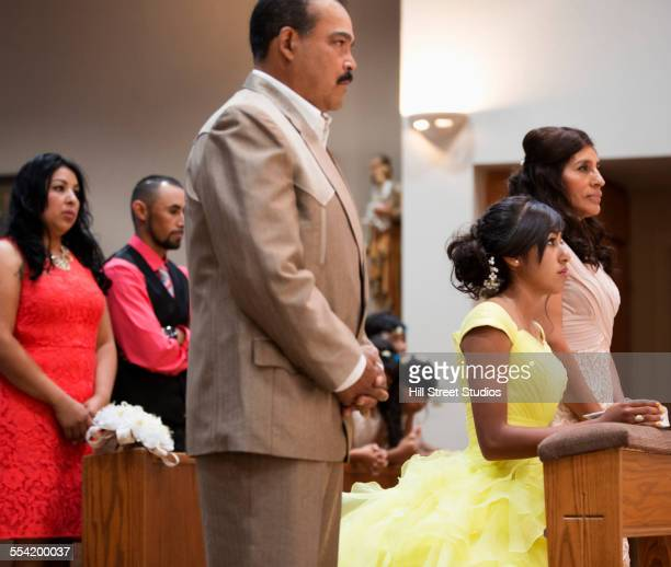 Hispanic family celebrating quinceanera in Catholic church