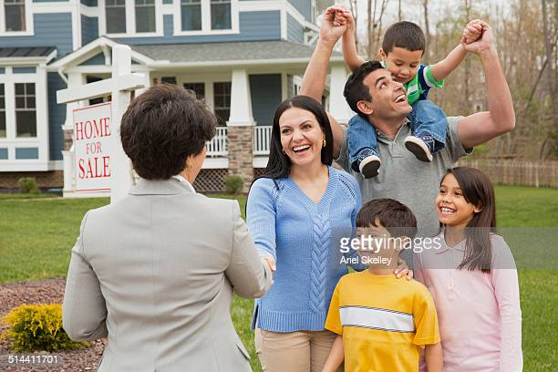 Hispanic family celebrating with broker outside new home