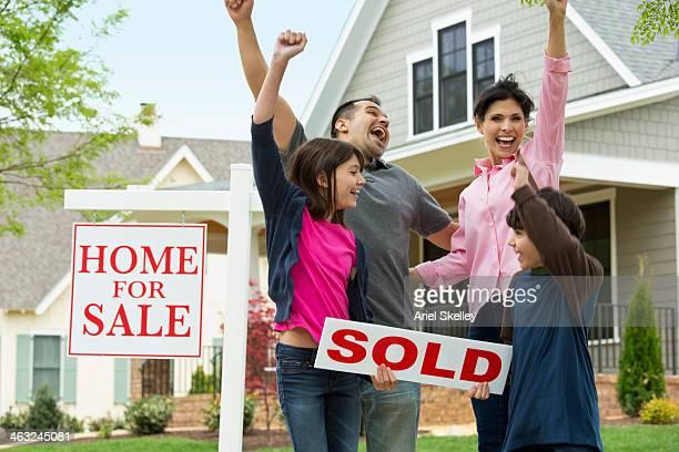 Hispanic family cheering by new house