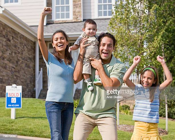 Hispanic family cheering in front of new house
