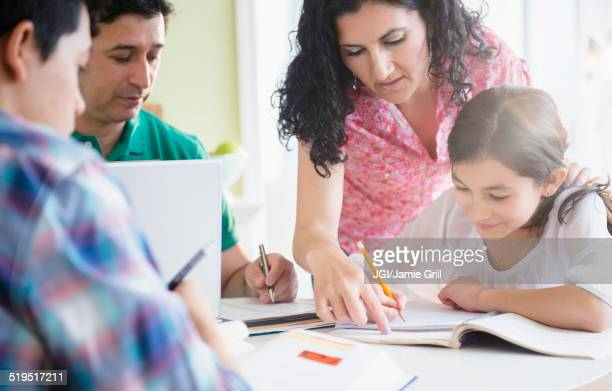 Hispanic family doing homework together at table