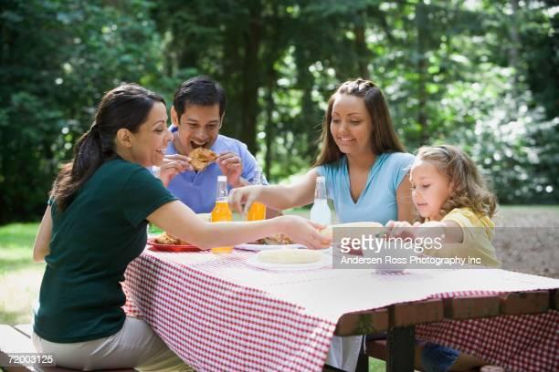Hispanic family eating at picnic table